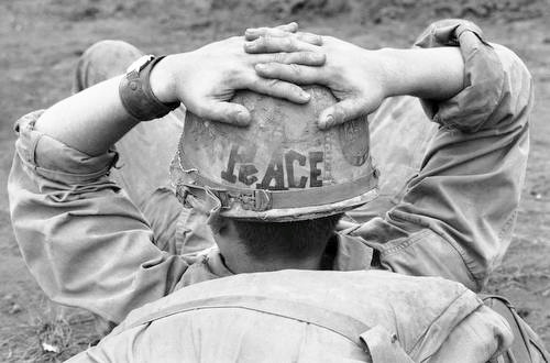"The helmet of SP/5 Mike Reeves, 19, of San Bernardino, Calif., was decorated with the word ""peace"" as he awaited a helicopter to airlift his unit from a fire support base in Vietnam on Jan. 12, 1971. A strand of love beads is attached to the helmet strap at left. Everywhere in Vietnam one can find sign of insubordination in the line units, hopelessness in the rear and general disgust with the war--the way it's being fought, the way it isn't being fought, the reason for its being fought at all. (AP Photo)"
